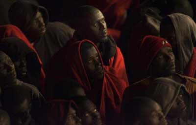 Migrants rest wrapped in blankets after arriving at Los Cristianos port on Spain's Canary Island of Tenerife early September 30, 2008. Some 229 would-be immigrants were rescued by Spanish rescue workers after being intercepted aboard a fishing boat adrift some 60 miles (96.5 km) offshore on their way to European soil from Africa, according to authorities. (REUTERS/Santiago Ferrero)
