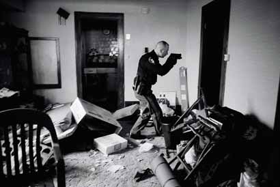 Extreme Caution When Detective Cole finds a home that is already abandoned or vacant, he enters with his weapon drawn, to guard against squatters. The World Press Photo judges chose this image as World Press Photo of the Year.